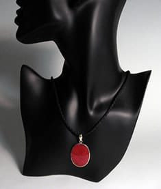 The Witches' Red Coral Amulet displayed on a black mannequin